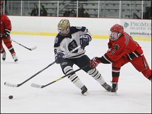 St. John's Jesuit player Nate Miller, 6, skates the puck away from Bowling Green High School player Dakota Bell, 9.
