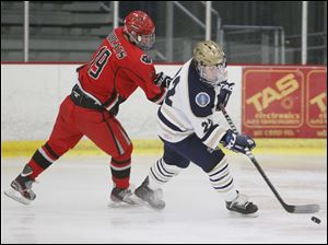 St. John's Jesuit player Jimmy Scott, 22, keeps the puck away from Bowling Green High School player Ryan Emans, 19.
