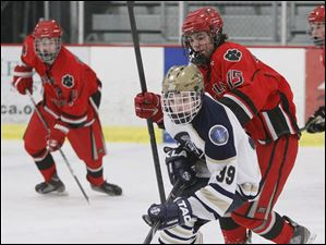 St. John's Jesuit player Nick Baumgartner, 39, skates the puck away from Bowling Green High School player Grant DeWitt, 15.