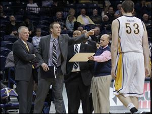Toledo assistant coach Jason Kalsow, 2nd from left, yells at his players as Nathan Boothe walks off the court during 2nd half.
