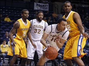 Toledo's Josh Lemons dribbles through McNeese's Jeremie Mitchell, left, Toledo's Reese Holliday and McNeese's Desharick Guidry.