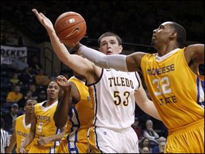 Toledo's Nathan Boothe and McNeese's Desharick Guidry reach for a rebound.