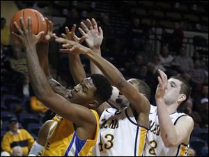 McNeese's Craig McFerrin grabs a rebound from Toledo's Matt Smith, center, and Nathan Boothe.