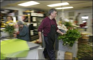 Mary Ann Myers, of Sylvania, left, puts the finishing touches on an order while Ken Myrice carries greens for floral arrangements at Emery's Flowers & Company.