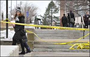 Pedestrians walk by police tape on the MIT campus today in Cambridge, Mass.,after police responded to reports of a gunman on campus that Cambridge police later said were unfounded.