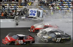 Kyle Larson (32) goes airborne into the catch fence in a multi-car crash including Dale Earnhardt Jr. (88), Parker Kligerman (77), Justin Allgaier (31) and Brian Scott (2) during the final lap today of the NASCAR Nationwide Series auto race at Daytona International Speedway.