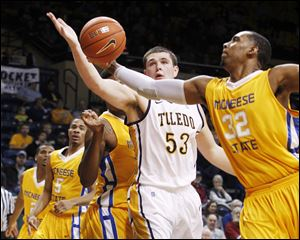 Toledo's Nathan Boothe and McNeese's Desharick Guidry reach for a rebound at Savage Arena.