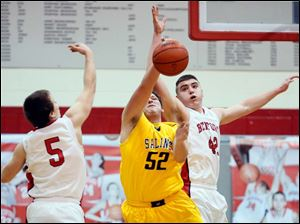 Bedford's Jeremiah Harris (42) and Bradley Boss (5) defend against  Saline's Michael Gale (52).