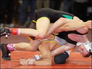 Delta wrestler Kyle Keller, top, works to turn Archbold's Damian Short to his back during their Division III 120 pound district final match. Keller won the match.