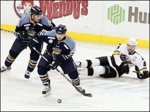 The Walleye's Patrick Knowlton, center, takes the puck away from Cincinnati's Jack MacLellan, right.
