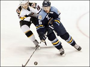The Walleye's Wes O'Neill fights for the puck with Cincinnati's Trevor Lewis.