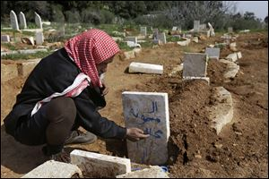 Abu Ibrahim, 73, writes his granddaughter's name on her grave in Syria, a victim of an airstrike. The U.N. estimates 70,000 people have been killed in the civil war.