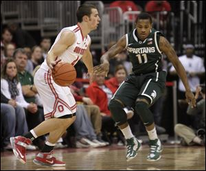 Ohio State's Aaron Craft, left, looks for an open pass as Michigan State's Keith Appling defends. Craft scored 21 points.