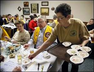 Julie Delrue serves dessert to Bedford Lions Club members  during a meeting Wednesday at the Erie Restaurant in Erie. The club meets at the restaurant twice a month.