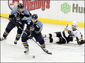 The Walleye's Patrick Knowlton, center, takes the puck away from Cincinnati's Jack MacLellan at the Huntington Center.