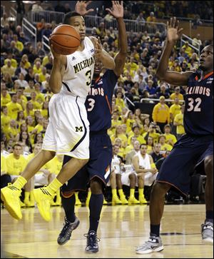 Michigan guard Trey Burke, left, passes as Illinois' Brandon Paul, center, and Nnanna Egwu defend Sunday in Ann Arbor. The Wolverines won 71-58.
