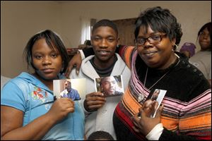 Some of La'Sean Robinson's siblings show pictures of the murder victim. From left are Latosha, James, and Lautricia Robinson, gathered in Toledo.