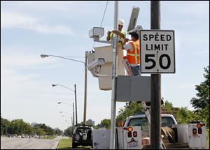 Andy Orshoski of National Light and Power in Sandusky, left, and David Burnham of Redflex Traffic Systems, Phoenix, install a speed monitoring camera on the Anthony Wayne Trail in Toledo.
