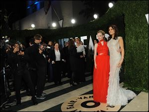 From left, actresses Samantha Barks and Amanda Seyfried arrive at the 2013 Vanity Fair Oscars party.
