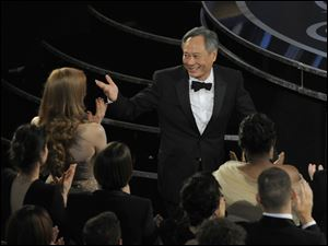 Ang Lee walks on stage to accept the award for best directing for