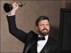 Ben Affleck lifts his Academy Award for best picture for