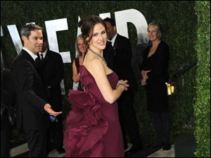 Actress Jennifer Garner displays the back of her dress as she arrives at the 2013 Vanity Fair Oscar party.