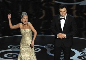 "Host Seth MacFarlane, right, and actress Kristin Chenoweth perform a song dedicated to the ""losers"" during the finale of the Oscars."