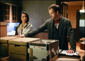 "Jonny Lee Miller, right, as Sherlock Holmes and Lucy Liu as Joan Watson in a scene from the series, ""Elementary."""