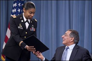 Secretary of Defense Leon Panetta hands the memorandum he has just signed, ending the 1994 ban on women serving in combat, to Army Lt. Col. Tamatha Patterson of Huntingdon, Tenn., during a news briefing at the Pentagon in Arlington, Va., in January.