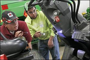 Penta students Marshall Kohl, 18, of Rossford, left, and Tanner Engle, 18, of Bowling Green, right, take a look at a forklift during the 20th annual FAA District I Agricultural and Industrial Diagnostics Contest. The competition pitted teams of two from local high schools against a clock to fix farm machinery.