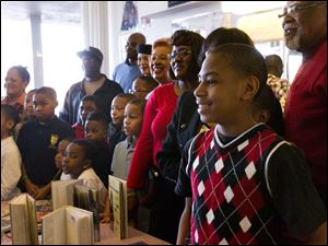 Daveon Duff, 12, center right, smiles as he stands for a photograph with other attendees of the 10th Annual Boys Booked On the Barber Shops Program at Blendz Barber Shop in Toledo.
