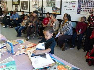 Camarr Burton, 5, checks out a book as members of several sponsoring organizations sit with attendees.