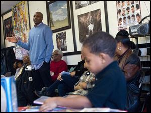 Camarr Burton, 5, right, thumbs through a book as Dennis Hopson, left, address attendees.