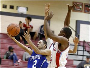 Springfield's Curtis Hassell (12) drives to the net against  Bowsher defenders.