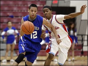 Springfield's Curtis Hassell (12) drives past Bowsher's Jeff Jones (4).