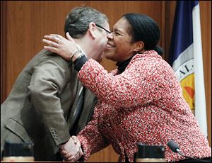 Councilman Rob Ludeman congratulates Paula Hicks-Hudson after she is sworn in as the president of Toledo City Council. Republican Tom Waniewski cast the only 'no' ballot in Tuesday's vote.