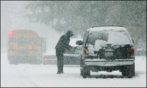 Juan Chavez, of Mundelein, Ill  clears the snow from his car during a snow storm today in Mundelein, Ill.
