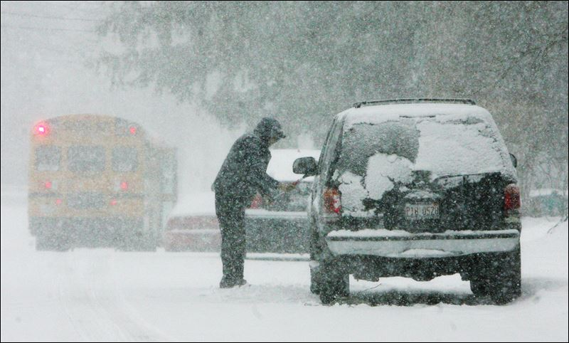 the snow from his car during a snow storm today in Mundelein, Ill