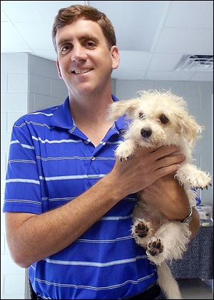 Gary Willoughby, an Ypsilanti, Mich., native, holds an adoptable dog at his former job in South Carolina.