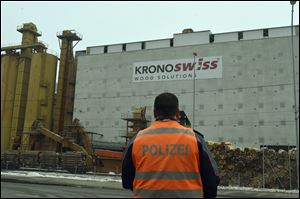 A police stands in front of a wood-processing company in Menznau, central Switzerland, today, where several people were killed in a shooting.