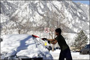 Adnan Reza, a senior engineering student at the University of Colorado, from Dhaka, Bangladesh, removes the snow from his car on a sunny morning following a winter storm, in Boulder, Colo.