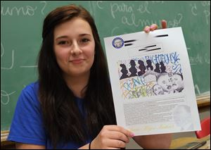 Sallie Fish, a seventh-grade student at St. Pius X School in Toledo, displays a copy of her winning entry in a statewide contest sponsored by the Ohio Civil Rights Commission.