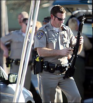 A California Highway Patrol officer loads an ammunition clip into his rifle near the shooting scene in Santa Cruz, Calif., where two Santa Cruz Police detectives were shot and killed Tuesday.