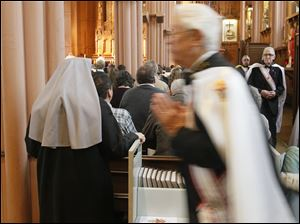 Sr. Mary Patricia of the Little Sisters of the Poor, left, as a member of the Knights of Columbus returns to his seat after Communion.