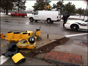 The wreckage of a traffic light rests on the ground on the Anthony Wayne trail near Woodsdale after an injury crash early today.
