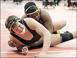 Whitmer's Marquise Moore, top, records the winning takedown in to defeat Massillon Perry's  Stefano Millin 3-1 in overtime in a 285-pound match Thursday.