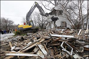 Workers demolish a home on Brewster Street that has sat vacant since 2007, resulting in depressed home values. The Ohio Attorny General's office is promoting  national mortgage settlement money to help fund the demolitions in blighted neighborhoods. Toledo hopes to remove 900 vacant houses.