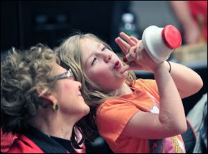 Trumpeter Gloria Buck of Walbridge watches as her granddaughter, Sylvia Freeman, 7, of Perrysburg, plays a silent solo on a trumpet mute at an Owens Community College Band rehearsal Feb. 18 at the college in Perrysburg Township.