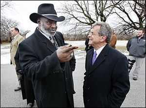 Mayor Mike Bell and Ohio Attorney General Mike DeWine talk about neighborhood issues in front of a home being demolished.