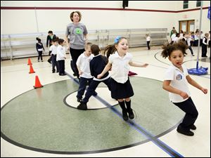 Ayla Tucker, 6, at center, and Marissa Fitzpatrick, 6, at right jump around.